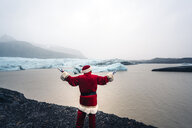 Iceland, back view of Santa Claus standing in front of glacier - OCMF00173