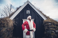 Iceland, Santa Claus standing in front of cabin looking at distance - OCMF00179