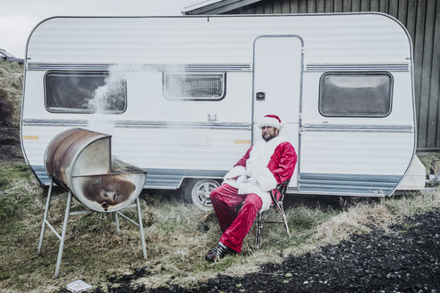 Iceland, Santa Claus sitting in front of caravan barbecueing - OCMF00182