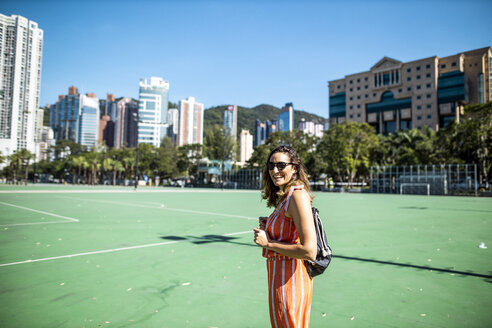 Hong Kong, Causeway Bay, Victoria Park, portrait of laughing woman on a sports field - DAWF00775