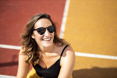 Portrait of happy woman wearing sunglasses on a sports field - DAWF00793