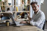 Portrait of businessman using laptop at desk - GIOF05064