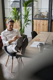 Businessman sitting with feet on desk using cell phone - GIOF05070
