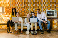 Group of smiling people sitting on couch in vintage living room with laptops - GIOF05085
