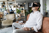 Mature man wearing VR glasses sitting on couch in a loft - GIOF05094