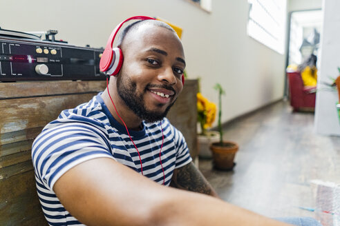 Portrait of smiling young man with headphones sitting on floor in a loft - GIOF05115