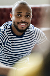 Portrait of smiling young man wearing striped t-shirt - GIOF05133