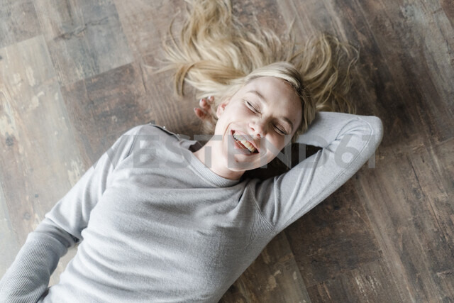 Happy blond young woman lying on wooden floor - GIOF05139 - Giorgio Fochesato/Westend61