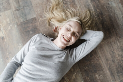 Happy blond young woman lying on wooden floor - GIOF05139