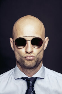Portrait of bald businessman wearing mirrored sunglasses pouting mouth - DAWF00824