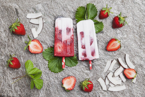Homemade strawberry coconut ice lollies with fresh strawberries and coconut slices on granite - GWF05711