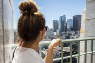 USA, California, Los Angeles, woman looking at the city from observation point - DAWF00836