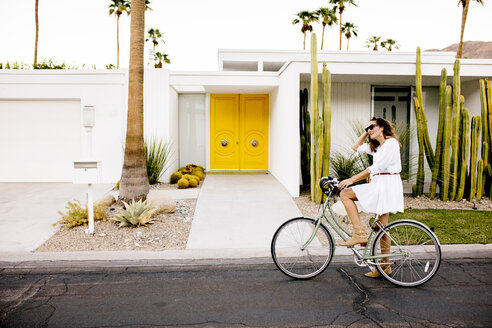USA, California, Palm Springs, woman on bicycle on the street - DAWF00863