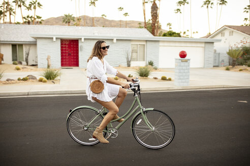 USA, California, Palm Springs, smiling woman riding bicycle on the street - DAWF00869