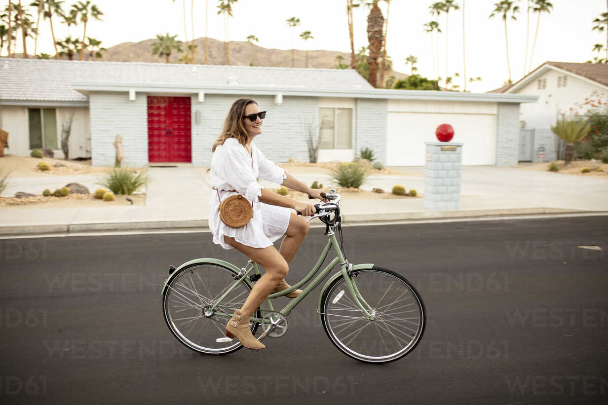 USA, California, Palm Springs, smiling woman riding bicycle on the street - DAWF00869 - Daniel Waschnig Photography/Westend61
