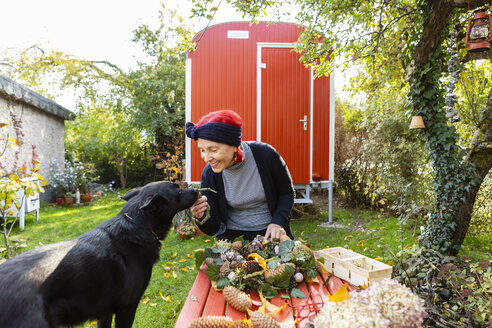 Smiling senior woman with red dyed hair stroking her dog while tinkering autumnal decoration - OJF00296