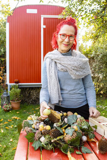 Portrait of smiling senior woman with red dyed hair tinkering autumnal decoration in the garden - OJF00302