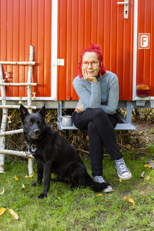 Portrait of content senior woman with red dyed hair sitting in front of red trailer in the garden with her dog - OJF00308