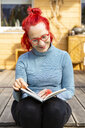 Portrait of smiling senior woman with red dyed hair sitting on terrace in front of her house reading a book - OJF00311