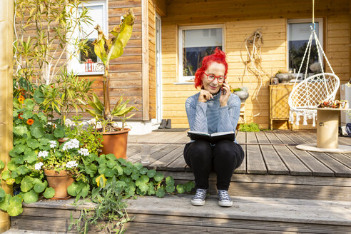 Smiling senior woman with red dyed hair on the phone sitting on terrace in front of her house reading a book - OJF00314