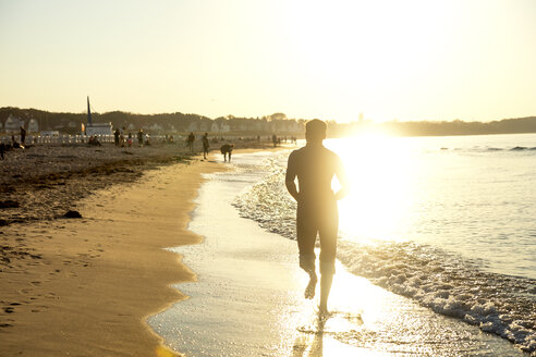 Man jogging at the beach at sunset - PUF01350