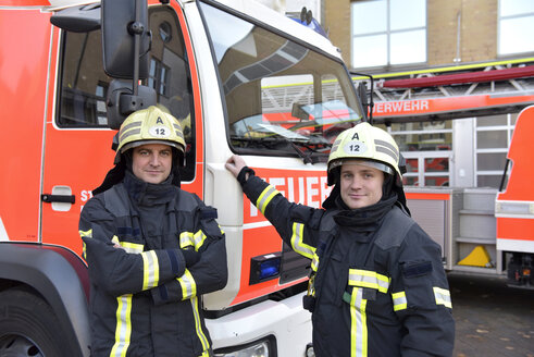 Portrait of two confident firefighters in front of fire engine - LYF00842
