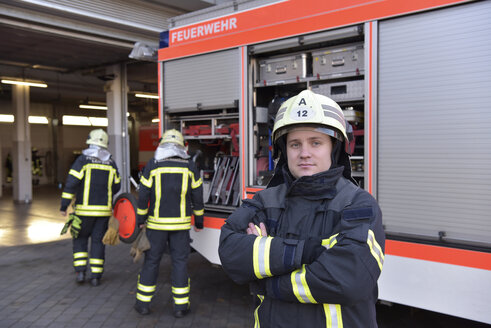 Portrait of confident firefighter in front of fire engine with colleagues in background - LYF00845