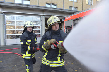 Two firefighters standing on yard exercising with extinguishing water - LYF00848