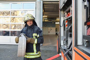 Portrait of firefighter at fire engine holding firehose - LYF00851
