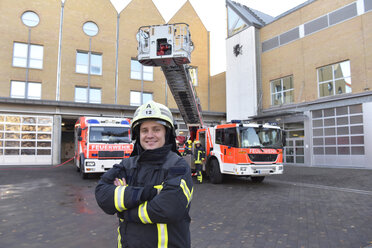 Portrait of smiling firefighter in front of fire engine with colleagues in background - LYF00854