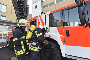 Two firefighters at fire engine preparing for an operation - LYF00857