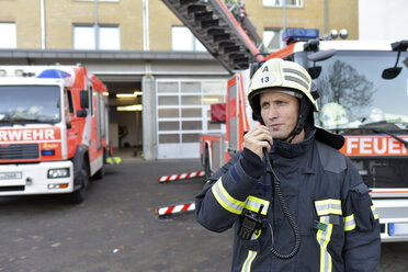 Firefighter standing on yard at fire engine using walkie talkie - LYF00860
