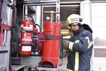Firefighter standing at fire engine with fire extinguisher - LYF00863