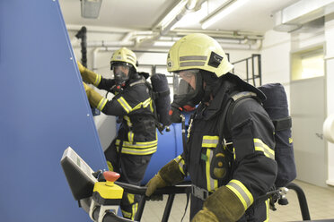 Two firefighters with respirator and air tank exercising in exercise room - LYF00866