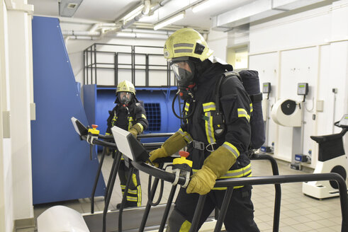 Two firefighters with respirator and air tank exercising in exercise room - LYF00869