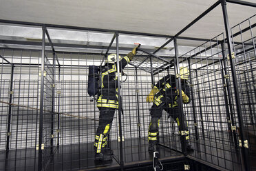 Two firefighters with respirator and air tank exercising - LYF00872