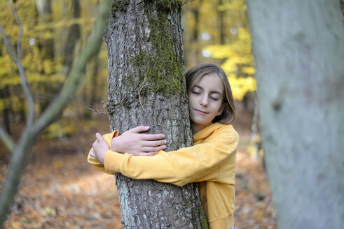 Portrait of girl with eyes closed hugging tree in autumnal forest - BFRF01942