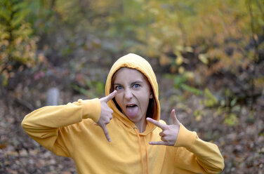 Portrait of girl wearing yellow hooded jacket in forest showing Rock And Roll Sign and sticking out tongue - BFRF01945