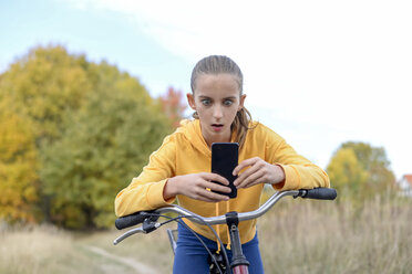 Portrait of girl leaning on bicycle starring at smartphone - BFRF01948