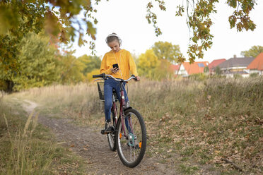 Girl with headphones sitting on bicycle looking at smartphone - BFRF01951