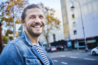 Portrait of bearded young man in the city laughing - FMKF05343