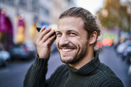 Portrait of laughing young man using smartphone on the street in the evening - FMKF05346