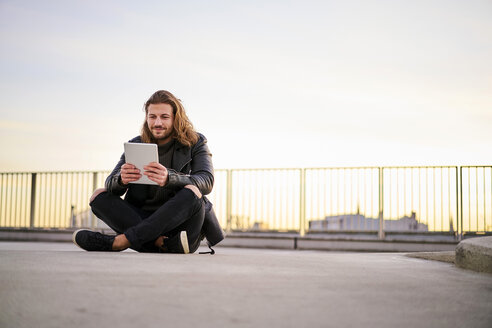 Portrait of bearded young man sitting on parking level at twilight using digital tablet - FMKF05349