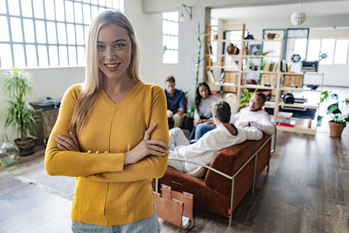 Portrait of smiling young businesswoman with coworkers in background in loft office - GIOF05163