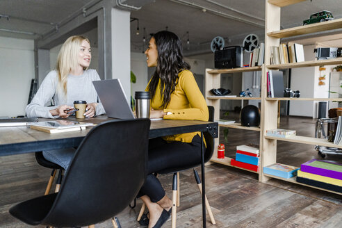 Two young businesswomen talking at conference table in loft office - GIOF05208
