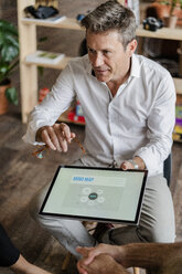 Businessman explaining a mind map on tablet screen during a presentation in loft office - GIOF05232