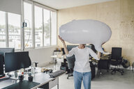 Woman standing in office, holding inflatable speech bubble in front of her face - RIBF00773