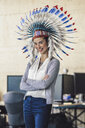 Young woman wearing Indian headdress, standing in office, with arms crossed - RIBF00788