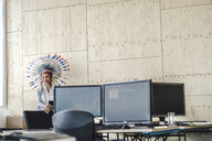 Young woman wearing Indian headdress, standing in office - RIBF00791