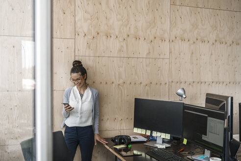 Young woman working in office, using smaftphone, laughing - RIBF00794